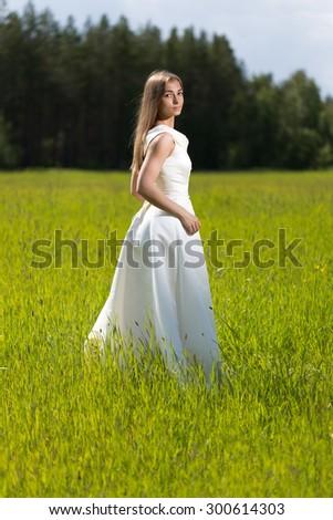 Beautiful girl in a wedding dress in the field. - stock photo