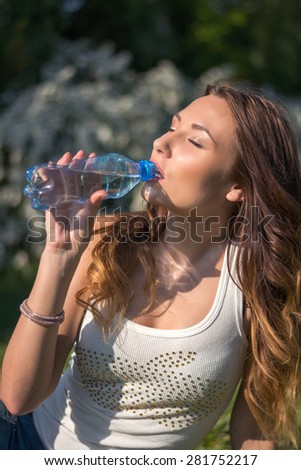 Beautiful girl in a white shirt is drinking water from a bottle in the park - stock photo