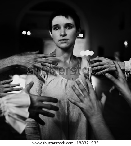 """beautiful girl in a white vintage transparent  dress as sacrifice, surrounded by crowd hands (art photo project """"Joan of Arc"""") - stock photo"""