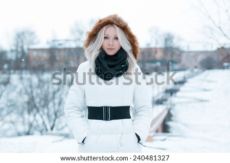 Beautiful girl in a winter jacket in the park - stock photo