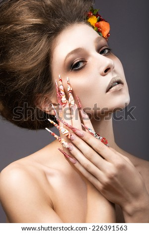 Beautiful girl in autumn image with long nails with bright and unusual make-up. Picture taken in the studio on a gray background - stock photo
