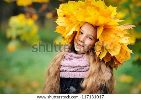 Beautiful girl in autumn leaves. Yellow maple wreath on his head. Happy baby. - stock photo