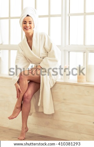 Beautiful girl in bathrobe is applying body lotion on her legs and smiling while sitting in bathroom - stock photo
