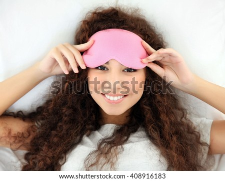 Beautiful girl in bed with eye mask - stock photo