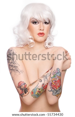 Beautiful girl in blond wig with stylish make-up and tattooed arms - stock photo