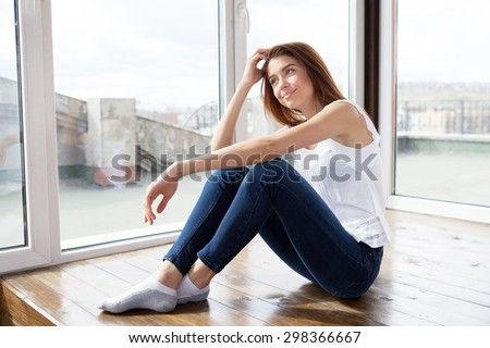 beautiful girl in blue jeans sitting on the floor and smiling - stock photo
