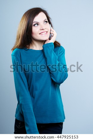 beautiful girl in blue shirt talking on the phone and smiling - stock photo