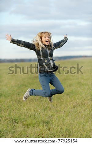 Beautiful girl in coat jumps against autumn field. - stock photo