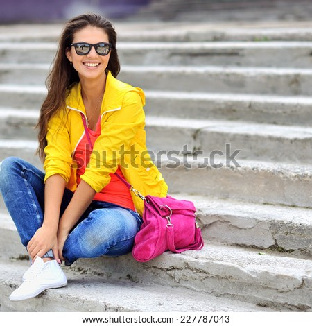 Beautiful girl in colorful clothes wearing sunglasses  - stock photo