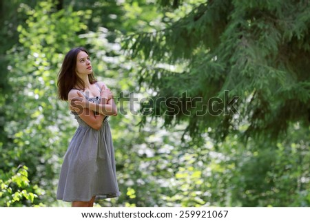 Beautiful girl in dress with long hair standing in woods on opposite branches of big tree - stock photo