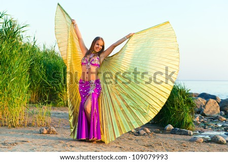 beautiful girl in east dress on seacoast before a sunset - stock photo