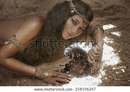Beautiful girl in ethnic jewelry with the mirror covered with sand  - stock photo