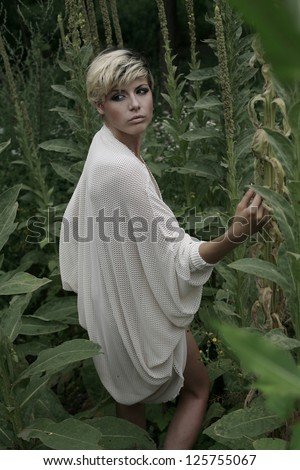 beautiful girl in exotic green nature looking over her shoulder - stock photo