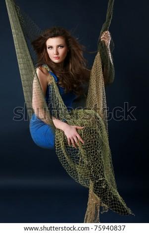 Beautiful girl in fishnet on dark-blue background - stock photo