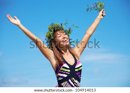 beautiful girl in floral wreath opened her hands at the blue sky - stock photo