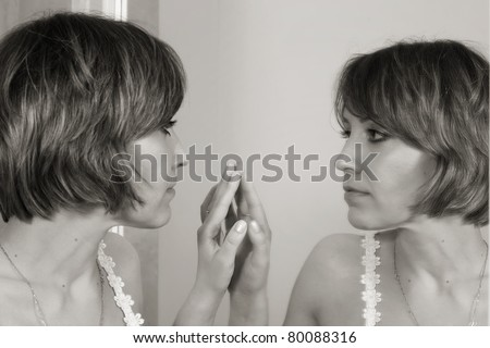 Beautiful girl in front of the mirror - stock photo