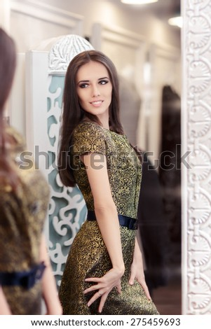 Beautiful Girl in Golden Brocade Dress Looking in the Mirror - Portrait of a young woman in a dressing room wearing new gown   - stock photo