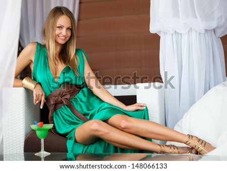 Beautiful girl in green dress with cocktail on summer terrace  - stock photo