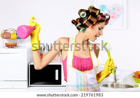 Beautiful girl in hair curlers in kitchen - stock photo