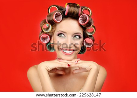 Beautiful girl in hair curlers on red background - stock photo