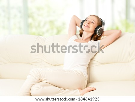 beautiful girl in headphones enjoying music at home on the couch - stock photo