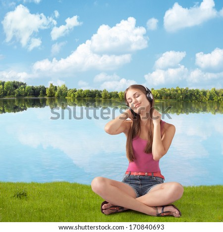 beautiful girl in headphones listens to music near river, sitting ashore  - stock photo