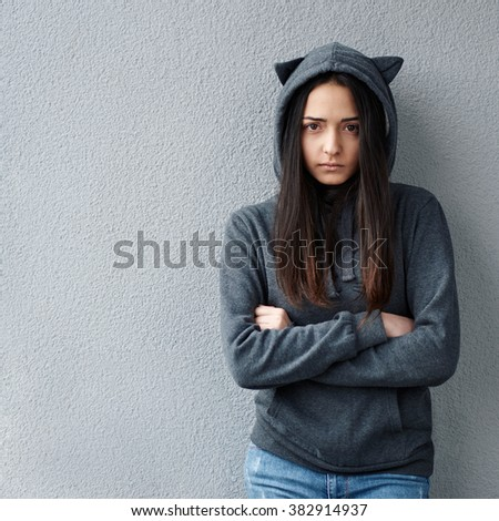 Beautiful girl in hood with cat's ears looking at camera against of texturew wall. - stock photo