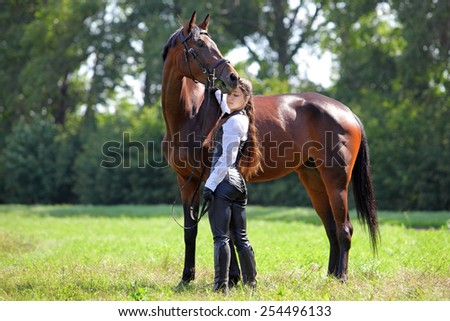 Beautiful girl in medieval clothe poses with the bay horse - stock photo