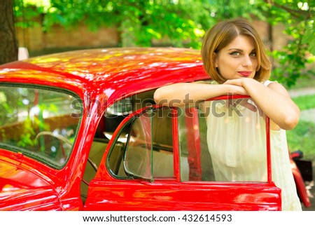 beautiful girl in pin-up style in a red car  Pin-up girl in white dress on the hood of red retro car on a background of green forest - stock photo