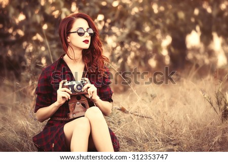 Beautiful girl in plaid dress retro camera and sunglasses at countryside - stock photo
