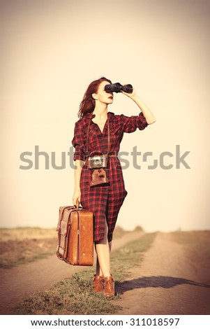 Beautiful girl in plaid dress with bag and binocular on countryside - stock photo