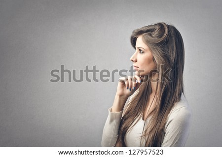 beautiful girl in profile on a gray background - stock photo