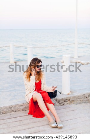 Beautiful girl in red dress and white jacket sits on a pier, smiles, and listens to music on earphones on a smartphone. Girl has ombre hair. She wears light brown espadrilles and dark sunglasses. - stock photo