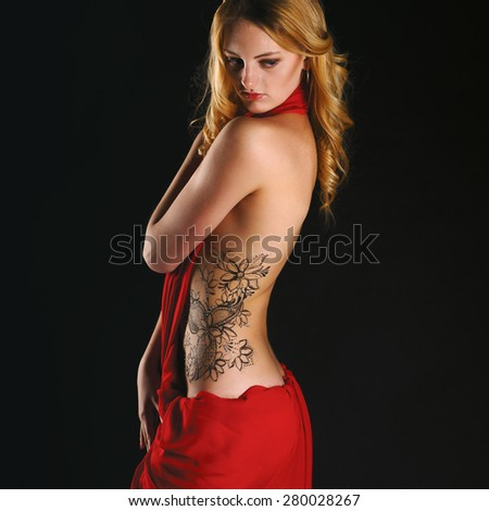 Beautiful girl in red dress back on black  - stock photo