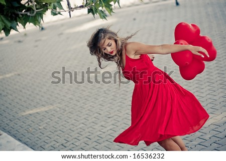 Beautiful girl in red dress moving with balloons as hearts - stock photo