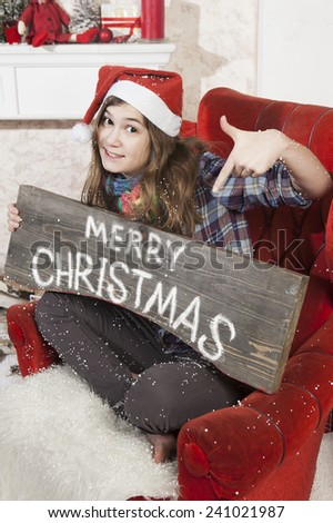 Beautiful girl in Santa Claus hat showing wooden signboard with Merry Christmas - stock photo