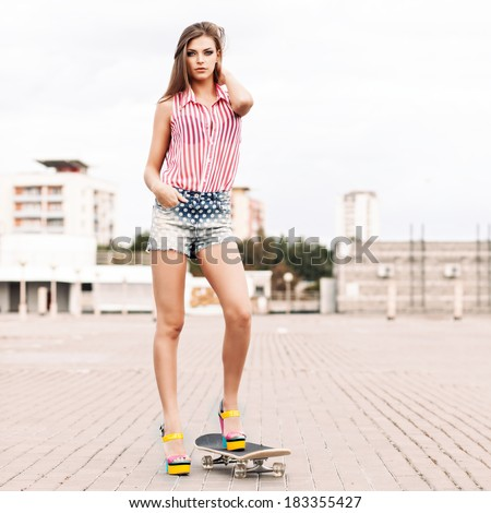 beautiful girl in short jeans shorts, sleeveless striped top and high heels stands on skateboard setting her long silky hair - stock photo