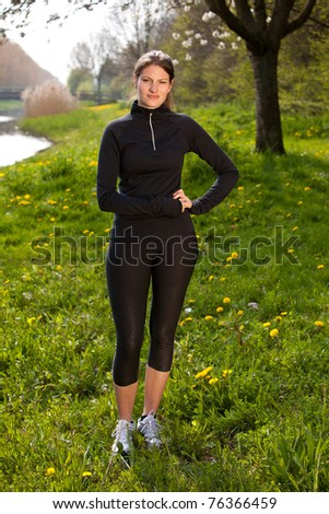 Beautiful girl in sports wear standing in a field - stock photo