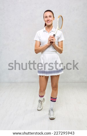 Beautiful girl in tennis dress, standing with a tennis racket in the hands of a white textured wall. - stock photo