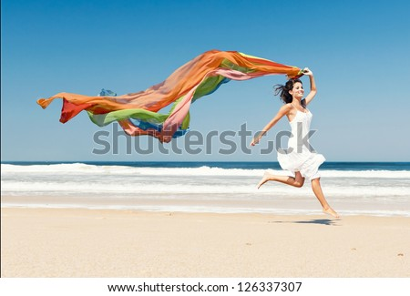 Beautiful girl in the beach running and holding a colored piece of fabric - stock photo