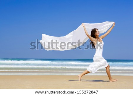 Beautiful girl in the beach running and holding a white piece of fabric - stock photo
