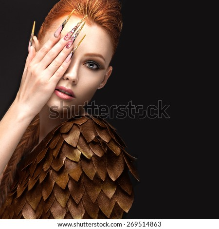 Beautiful girl in the image of the Phoenix with bright makeup, long fingernails and red hair. Beauty face. Picture taken in the studio on a black background. - stock photo