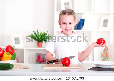 beautiful girl in the kitchen cooking vegetables - stock photo