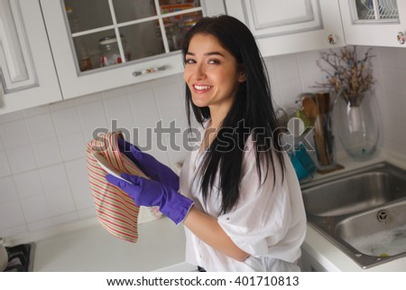 beautiful girl in the kitchen wiping the dish - stock photo