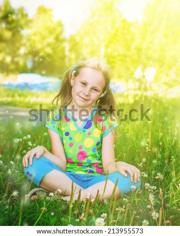 Beautiful girl in the meadow on a sunny summer afternoon. - stock photo