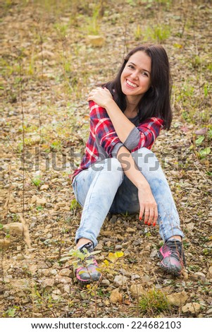 Beautiful girl in the mountains. Beautiful girl sitting on the ground. Girl resting, dreaming, looking mysterious.Travel, tourism, trekking in the mountains - The concept of active rest. - stock photo