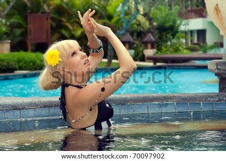 beautiful girl in the pool in the rain - stock photo