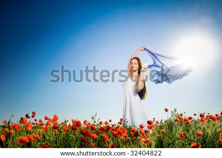 Beautiful girl in the poppy field, low angle view - stock photo