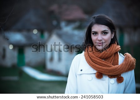 Beautiful girl in the winter coat standing near the winter resort,mountain chalets in the evening.December without snow.Tourist spending winter holidays at cottage in the mountains - stock photo