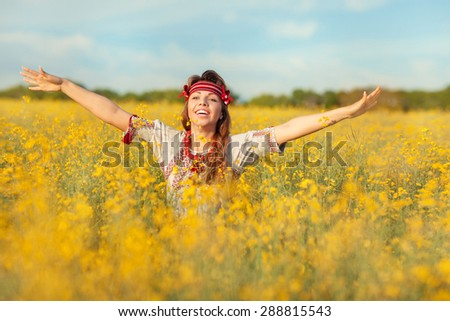 Beautiful girl in Ukrainian national dress is standing in a field of yellow flowers with outstretched arms. - stock photo